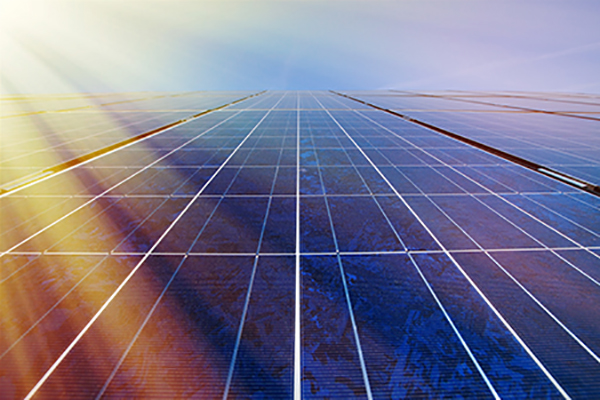 Solar panels and blue sky with sunlight shining on the panels